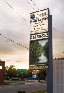 Live Oak FL Real Estate brokerage office sign, for United Country - Lands of North Florida Realty, Inc. 386-330-5332 phone number with a company logo and a picture of the Suwannee River also on the sign.