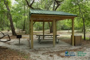 Royal Springs Picnic pavilion with table, grill, trash receptacle under big oak trees.